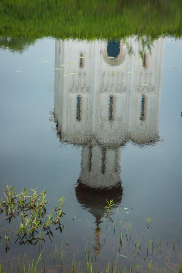 Reflexion av vitkyrkan med blåa kupoler och sceniska moln, Ryssland royaltyfria bilder