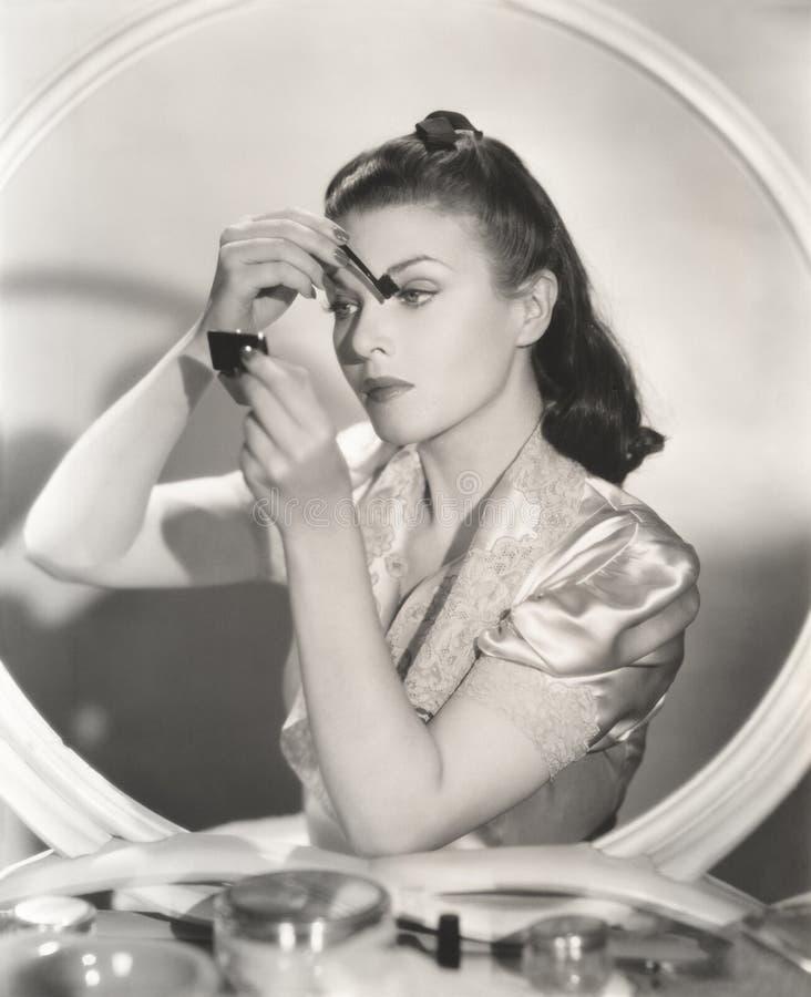 Reflexion der Frau im Spiegel, der Augenmake-up anwendet stockbild