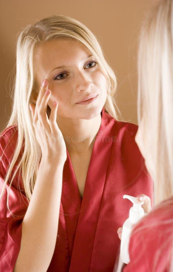 Reflexion der jungen blonden Frau, die Sahne verwendet stockfotos