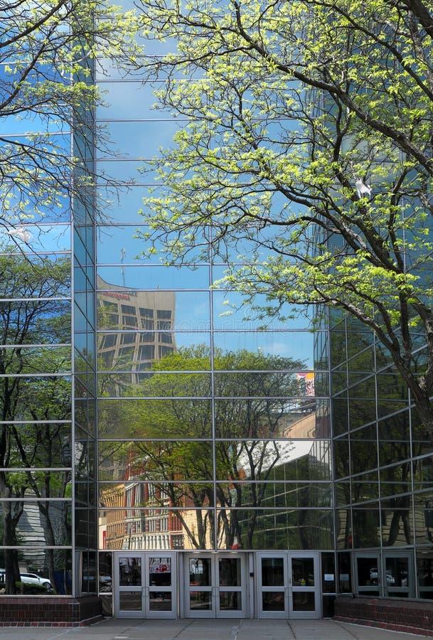 Reflexion der Straßengebäude und -bäume in den Fenstern eines modernen hohen Gebäudes mit einer Glasfassade lizenzfreie stockfotografie