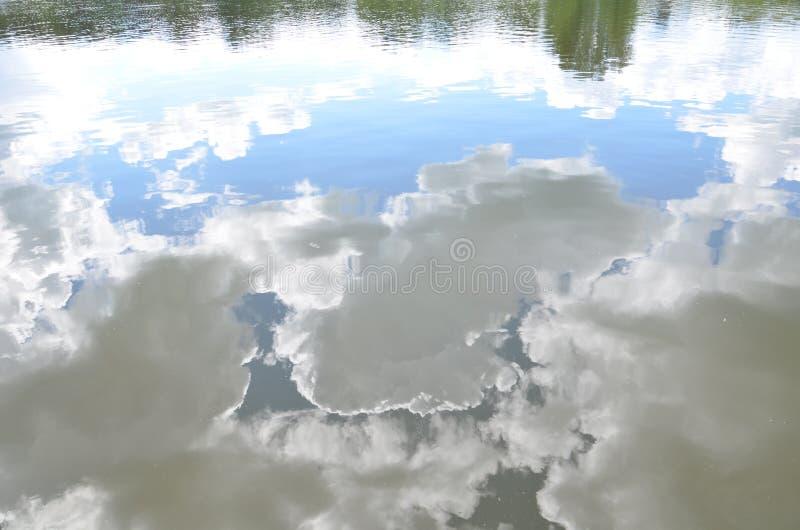 Reflexion des blauen Himmels mit weißen Wolken im Wasser, abstrakter Hintergrund lizenzfreie stockfotos