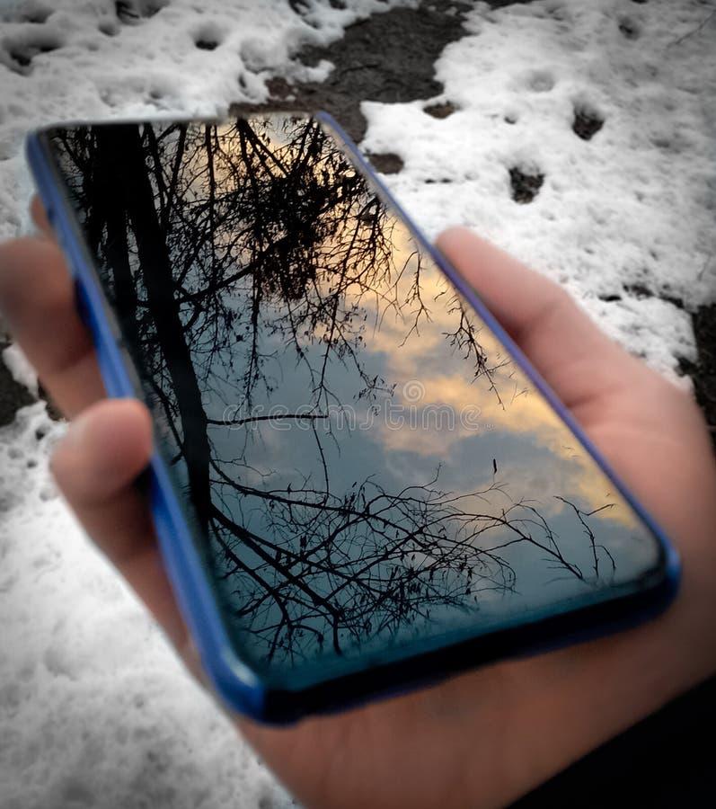 Reflexion des Himmels am Telefon, das in der Hand hält lizenzfreies stockfoto