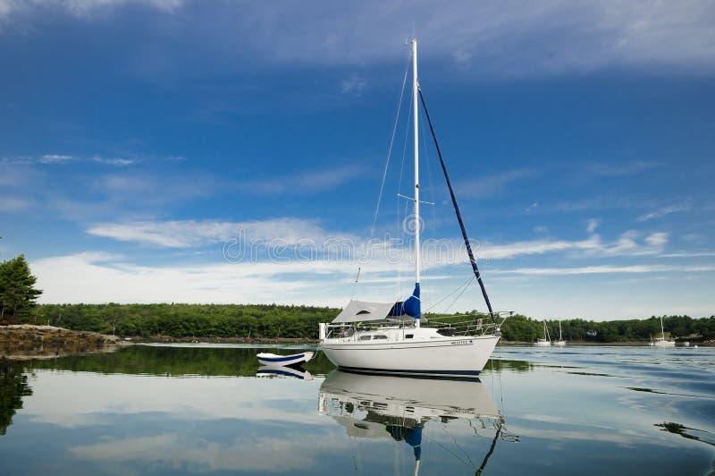 Reflexion des Segelboots auf glasigem Wasser lizenzfreies stockfoto