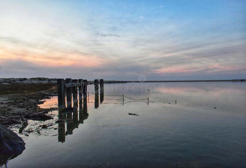 Reflexion des Sonnenuntergangs auf Wasser am Strand lizenzfreie stockfotografie