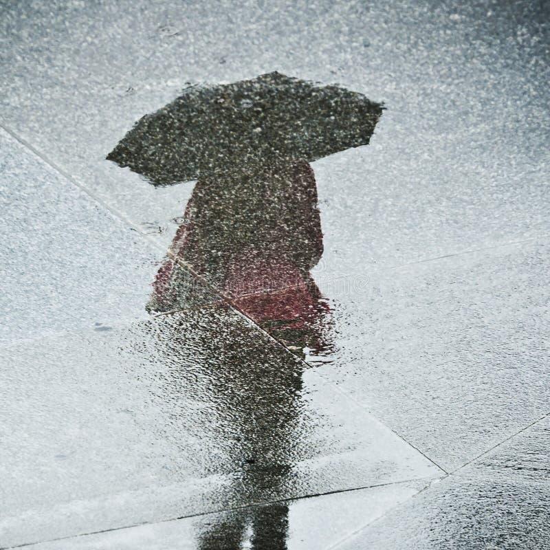 Reflexion einer Frau mit einem Regenschirm lizenzfreie stockfotos
