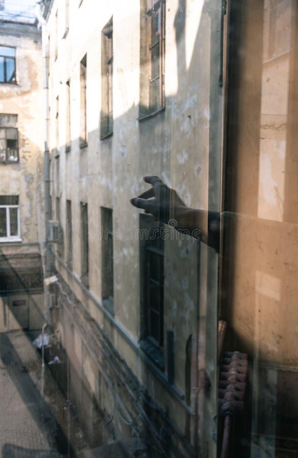 Reflexion einer Hand in einem Glasfenster lizenzfreie stockbilder