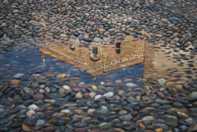 Reflexion einer Kirche in einer Pfütze stockbilder