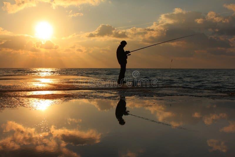 Reflexion eines Fischers an der Dämmerung lizenzfreies stockbild