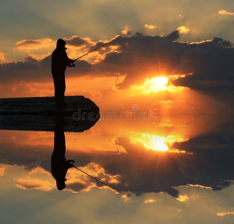 Reflexion eines Fischers im Wasser stockbilder