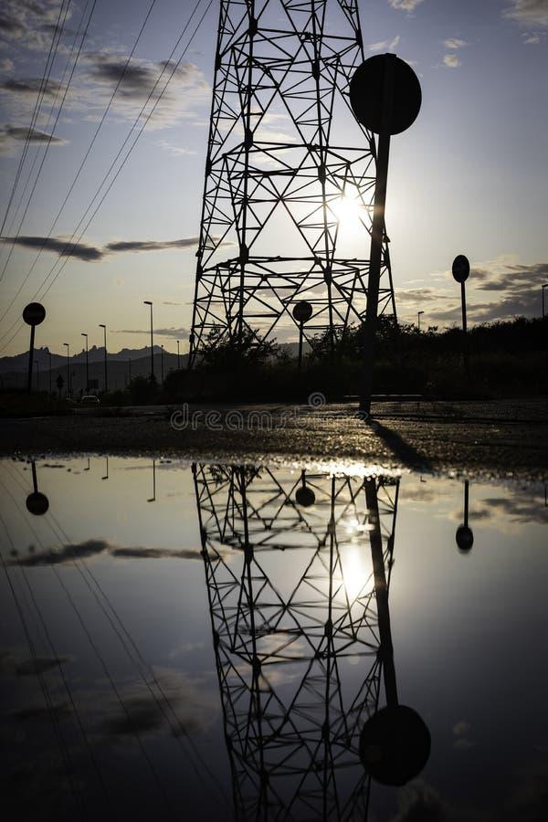 Reflexion eines Hochspannungsturms in einem Teich mit dem Himmel versteckt hinten an einem bewölkten Abend stockbild