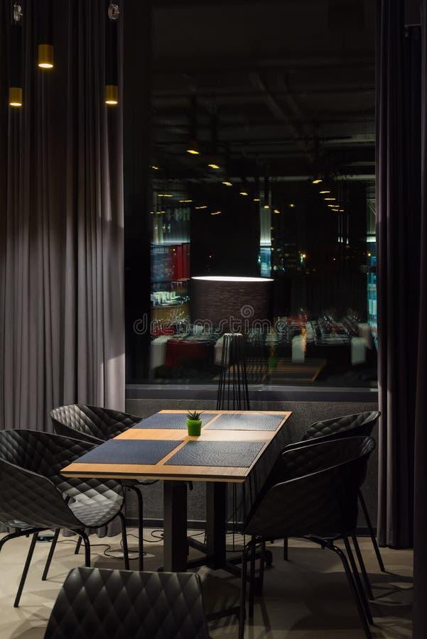 Reflexion för bakgrund för mörka färger för äta middag tabell för kafé inre arkivbild