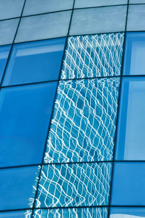 Reflexion i blå glasvägg av modern kontorsbyggnad royaltyfri bild