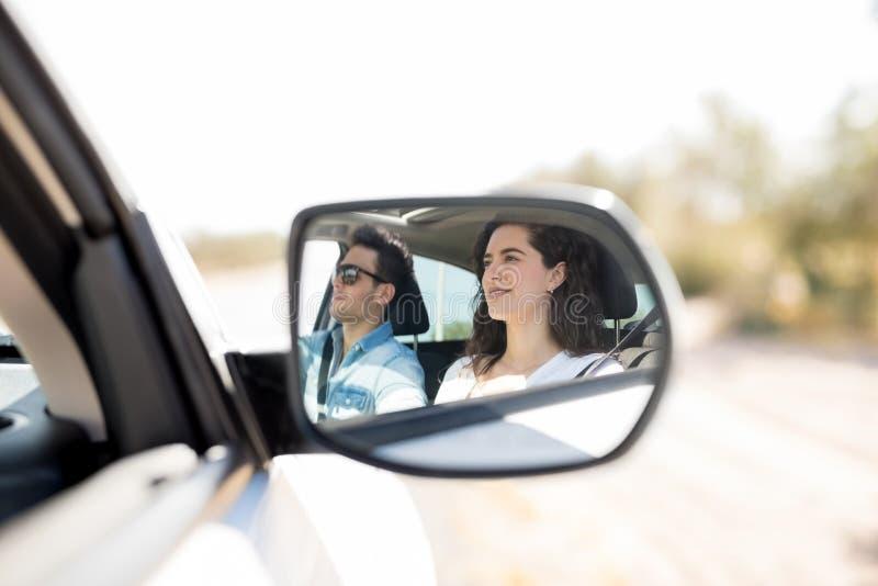 Reflexion im Seitenansichtspiegel von den Paaren, die mit dem Auto reisen stockbild