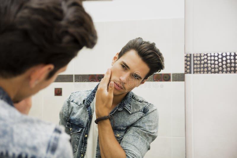 Reflexion im Spiegel des Mann-rührenden Gesichtes stockfoto