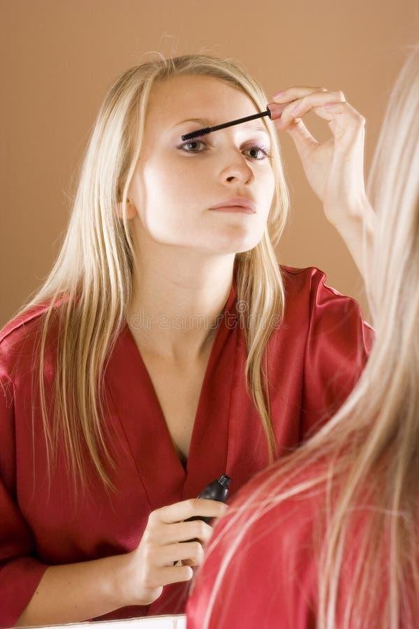 Reflexion junger blone Frau, die Wimperntusche setzt lizenzfreie stockbilder