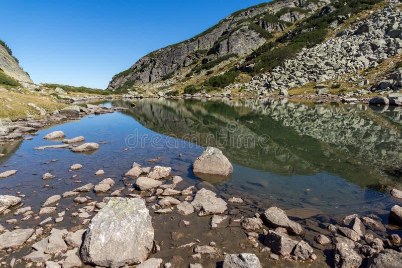 Reflexion von grünen Hügeln im kleinen See, Rila-Berg lizenzfreies stockfoto
