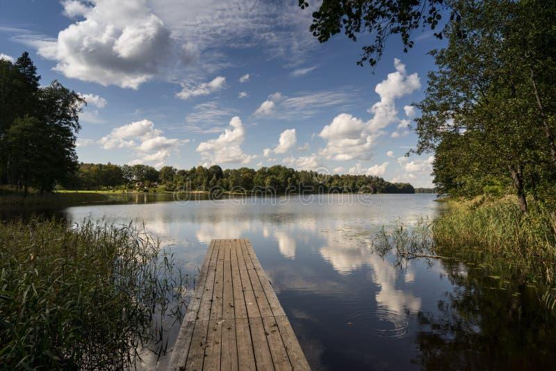 Reflexion von Wolken im See mit Promenade lizenzfreie stockbilder