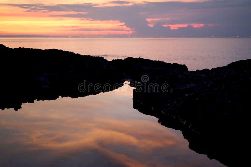 Reflexion von Wolken im Sonnenuntergang stockfotografie