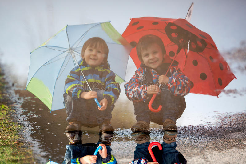Reflexion von zwei kleinen Jungen mit Regenschirmen lizenzfreies stockfoto