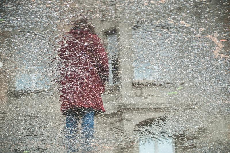 Reflexion of woman in puddle in the street stock images
