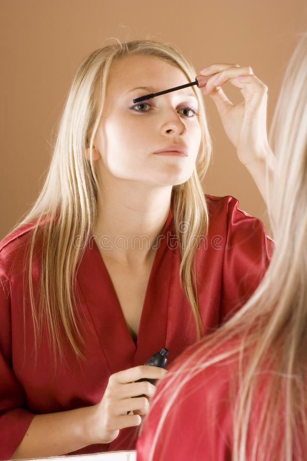 Reflexion of young blone woman putting mascara royalty free stock images