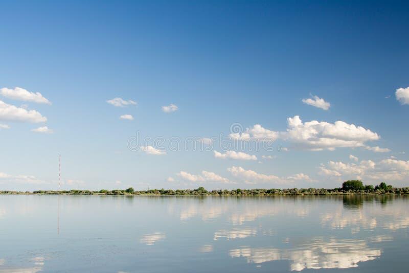 Reflexionen av en härlig himmel i parkerar sjön royaltyfria bilder