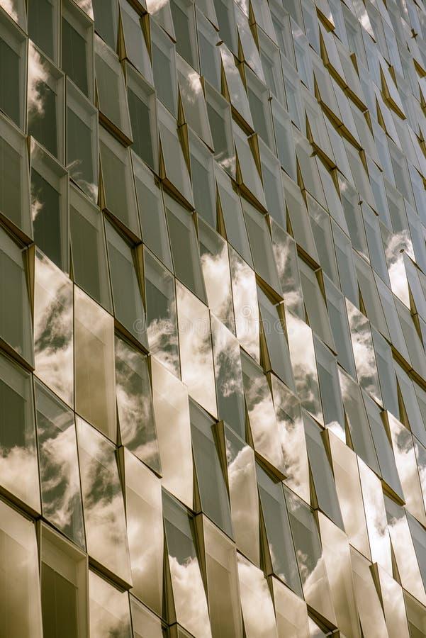 Reflexionen des bewölkten Himmels auf einer Glasfassade, Sepiaeffekt stockfotos