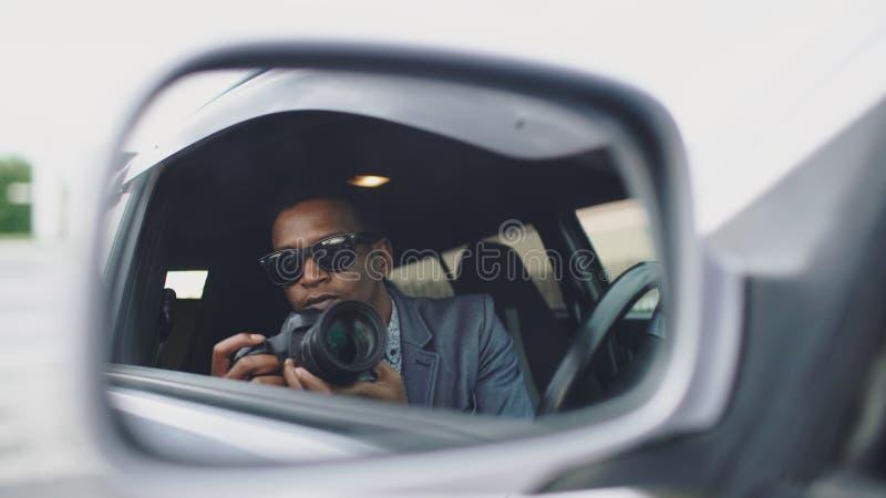 Reflexionen i sidospegel av Paparazzi man sammanträde inom bilen och att fotografera med dslrkameran arkivfoto