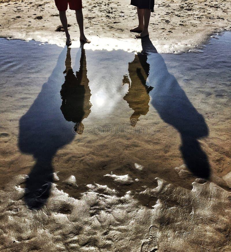 Reflexioner och högväxta skuggor på stranden arkivfoto