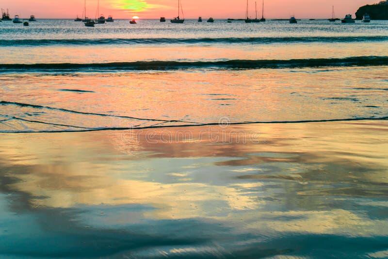 Reflexioner på strandvatten på solnedgång royaltyfri foto