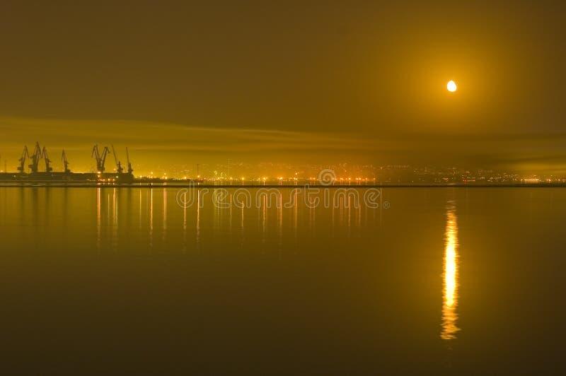 Reflexiones de la ciudad y de la luna en el mar Caspio fotos de archivo libres de regalías