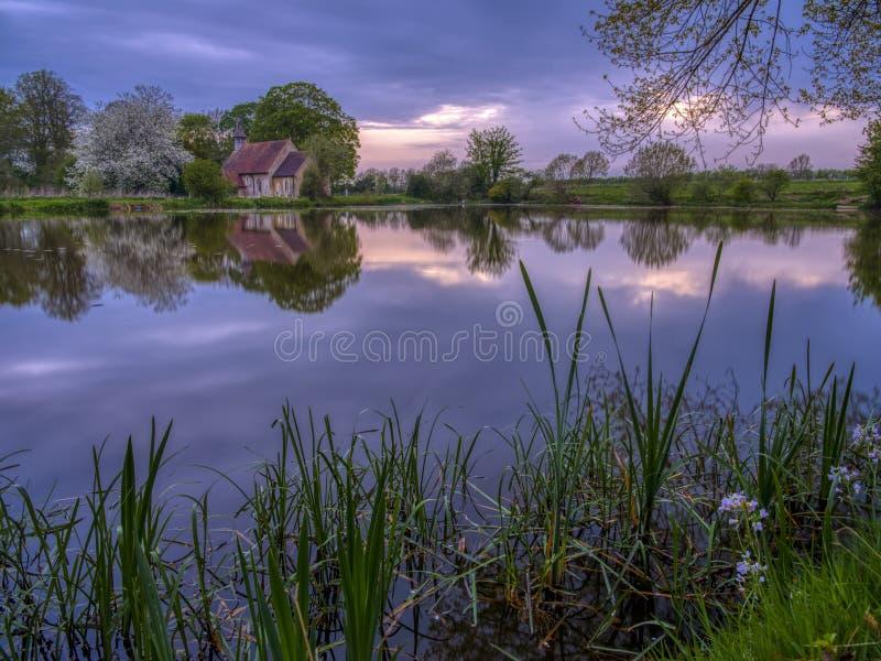 Reflexiones de la iglesia de St Leonard en Hartley Mauditt Pond, plumones del sur parque nacional, Reino Unido imagen de archivo libre de regalías
