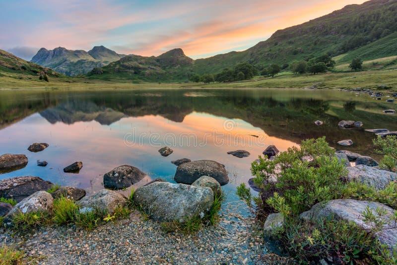 Reflexiones de la montaña en la salida del sol Blea distrito del Tarn, lago, Reino Unido fotografía de archivo libre de regalías