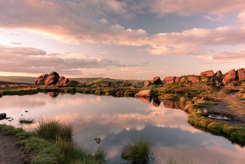Reflexiones de la piscina de Doxey, y puesta del sol en las cucarachas, en el parque nacional del distrito máximo, Staffordshire fotos de archivo libres de regalías