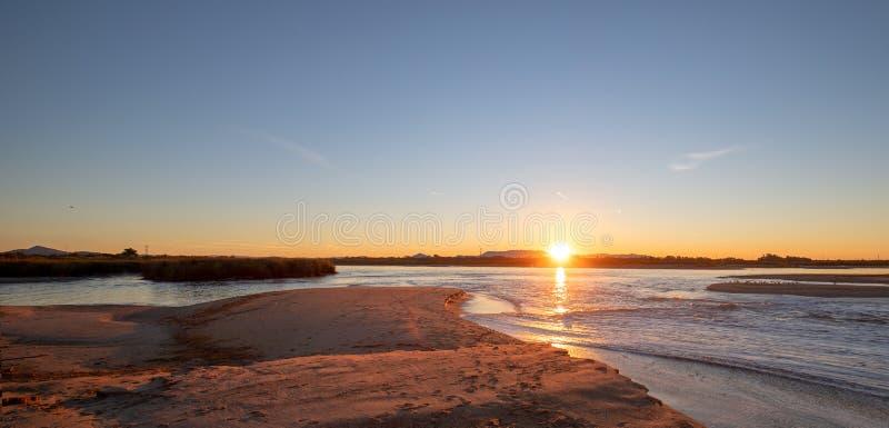 Reflexiones de la salida del sol sobre la salida de marea del estuario del río Santa Clara en el parque de estado de McGrath de V foto de archivo