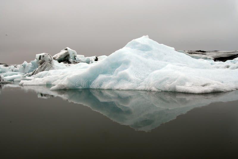 Reflexiones de los icerbergs azules y blancos cristalinos en agua oscura negra en la luz melancólica oscuro - glaciar de Jökulsár foto de archivo