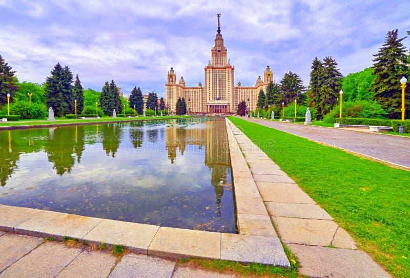 Reflexiones del edificio principal de la universidad rusa famosa en piscina de la cascada de la fuente debajo de las nubes dramát foto de archivo
