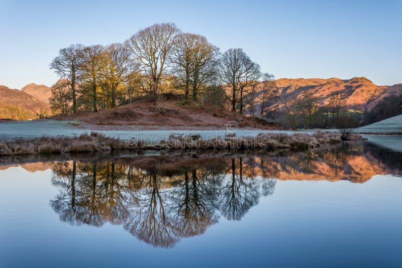 Reflexiones del invierno en el río Brathay imagenes de archivo