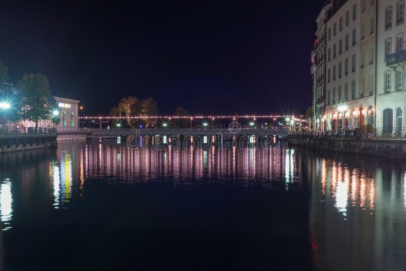 Reflexiones en el río Rhone en Ginebra en la noche foto de archivo