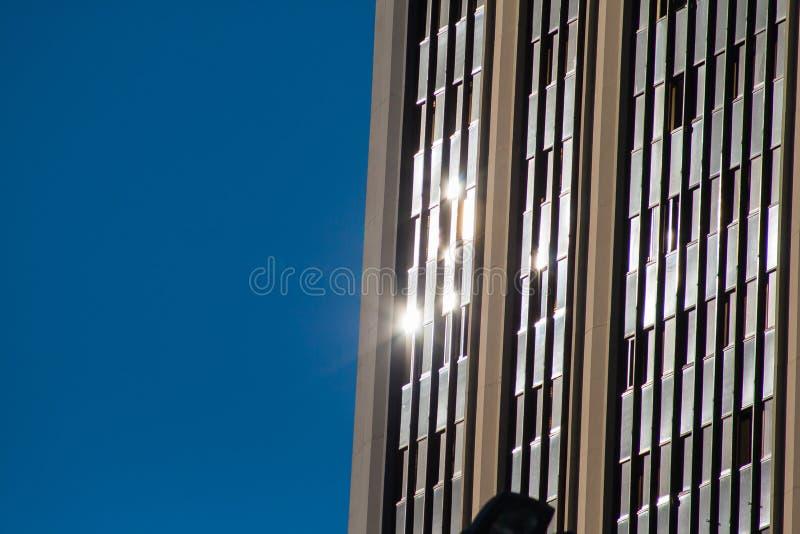 Reflexiones urbanas Los rayos de sol reflejaron sobre el vidrio de un edificio con el fondo azul imagenes de archivo