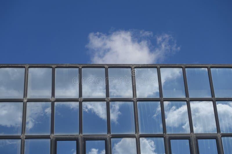 Reflexionsmoln och blå himmel på byggnadsfönster royaltyfri fotografi