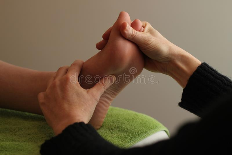 Reflexology en un pie que descansa sobre una toalla verde fotografía de archivo libre de regalías