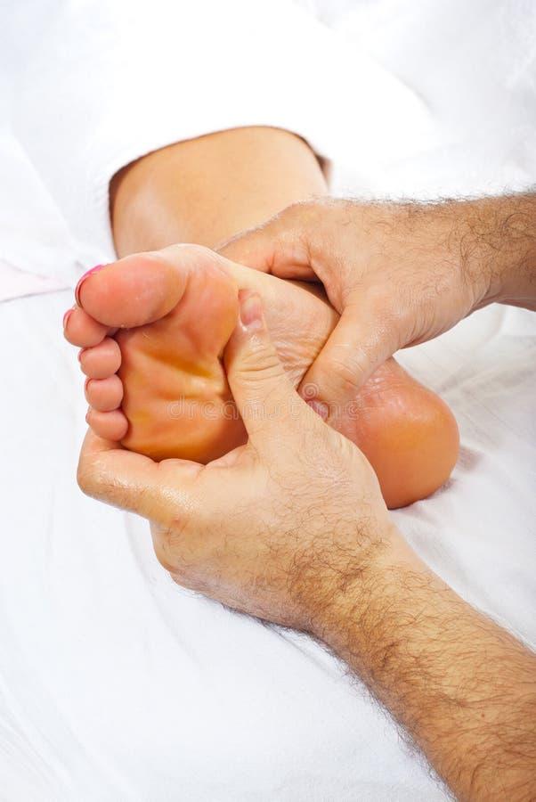 Reflexology foot massage. Professional masseur giving reflexology massage to woman foot stock photography