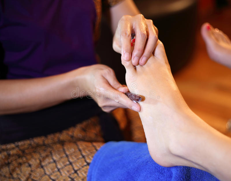 Reflexology foot massage, spa foot treatment by wood stick stock images
