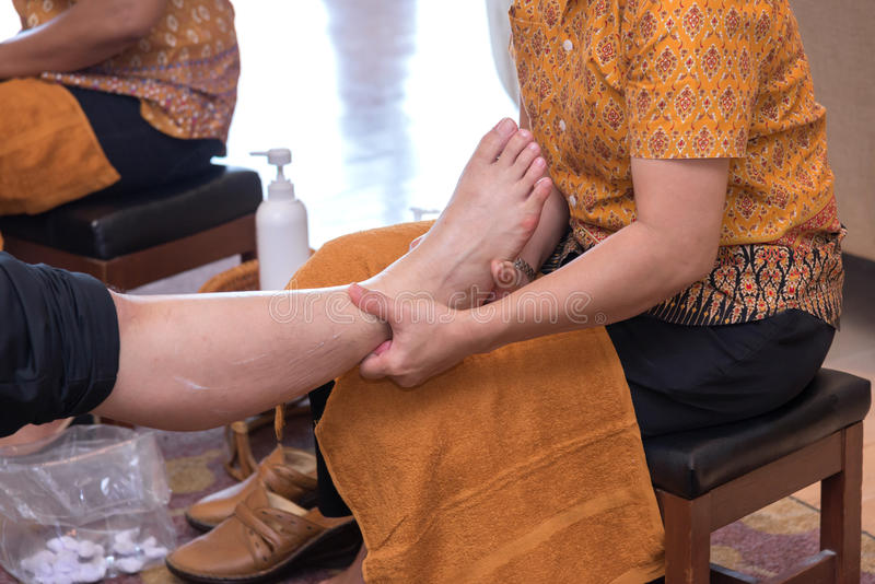 Reflexology foot massage in Thai spa treatment stock images