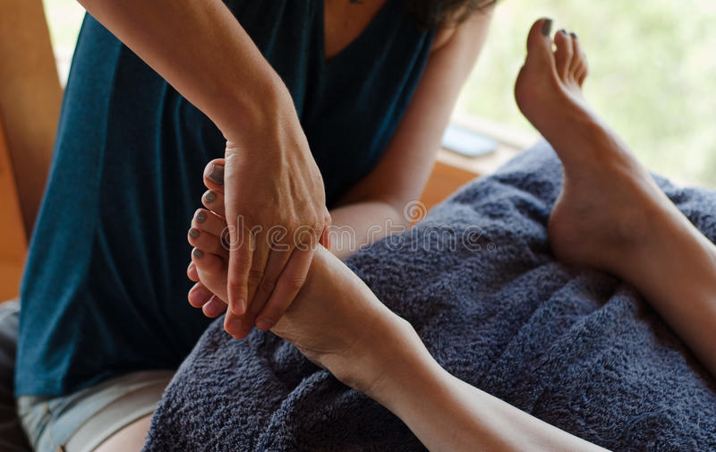 Reflexology Foot Therapist. Female therapist practicing reflexology on a female patient stock images