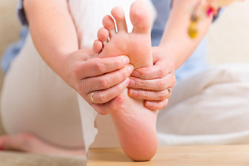 Reflexology. Hands doing feet reflexology or zone therapy at home stock photo