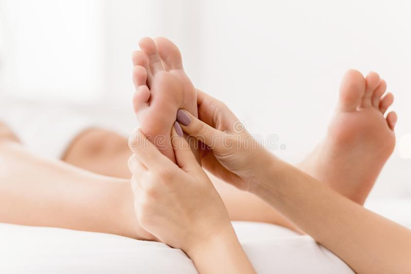 Reflexology. Massager pressing energy flow points on foot royalty free stock photos