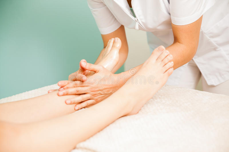 Reflexology session at a health spa. Closeup of the hands of a therapist in the middle of a reflexology session with a client at a health spa stock photography
