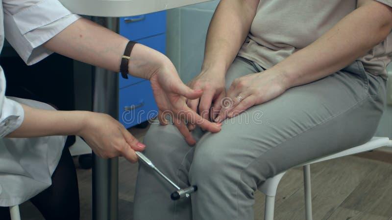 Reflexos dos testes do neurologista no martelo de utilização paciente fêmea foto de stock
